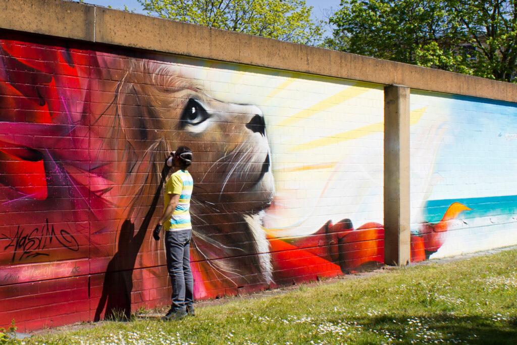 Mural (Wandgemälde/ Graffiti) von Nasim Naji, Streetart-BS an der Elbestraße in Braunschweig, Deutschland; Ausschnitt, Löwe; Sprühdose und Fassadenfarbe auf Wand; 2021
